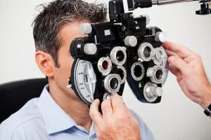 Optometrist adjusting panels of phoropter while examining his pa