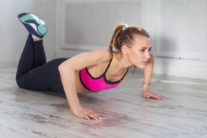 fitness athlete sportive woman sport model girl training doing push ups at home.