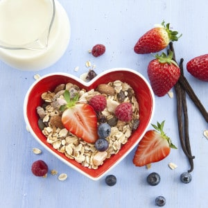 Muesli in heart-shaped bowl with fresh berries and milk
