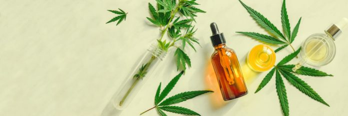 Different glass bottles with CBD OIL, THC tincture and cannabis leaves on yellow background. Flat lay, minimalism. Cosmetics CBD oil.